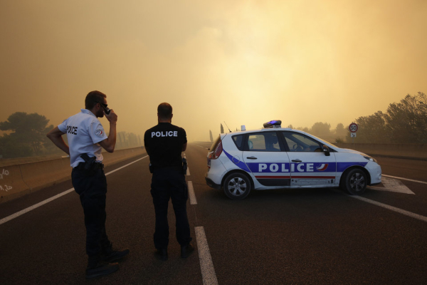 French police stand at a roadblock as smoke fills the sky and blocks the sun as fires burn north of Marseille