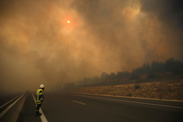 A French fireman watches as smoke fills the sky and partially blocks the sun as fires burn north of Marseille