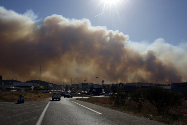 Smoke hangs low as it fills the sky while fires burn north of Marseille